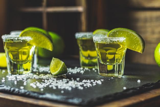 Mexicaanse gouden tequila geschoten met limoen en zout op zwarte stenen tafel oppervlak