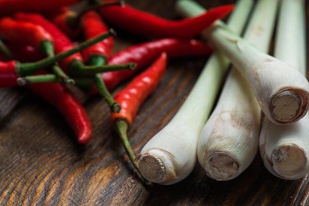 Mexicaanse hot chili peppers met citroengras verspreid over de houten tafel