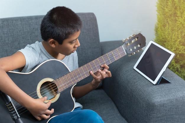 Mexicaanse jongen die thuis gitaarlessen volgt vanwege coronavirus, thuisonderwijs