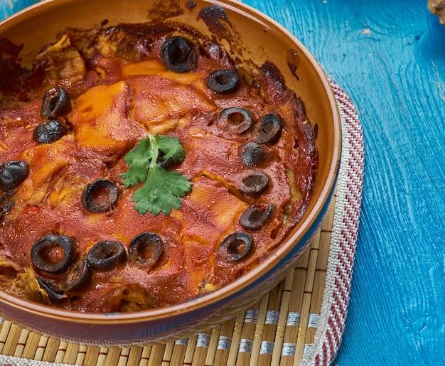 Mexicaanse keuken, traditionele rode chilaquiles met kip, diverse gerechten, bovenaanzicht.