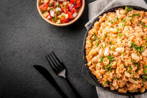 Mexicaanse, latijns-amerikaanse keuken. mexicaanse rijst- en bonenkom - recept gemaakt met rijst en witte bonen, zelfgemaakt, met verse kruiden en kruiden. in een koekenpan voor het koken, met salsa, bovenaanzicht copyspace