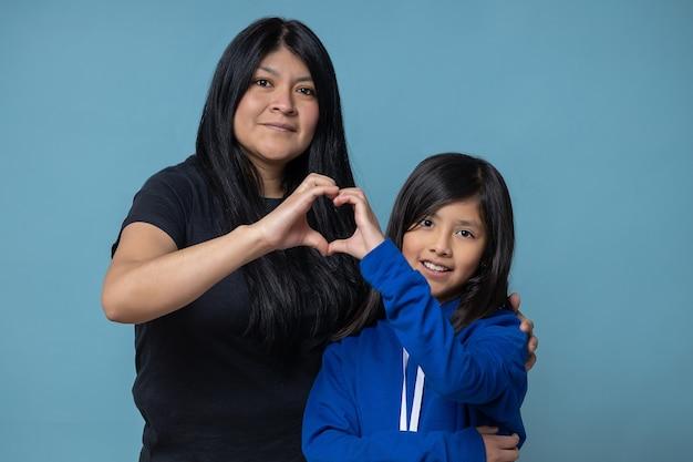 Mexicaanse moeder en dochter die een hart met hun geïsoleerde handen doen, meisjesmacht