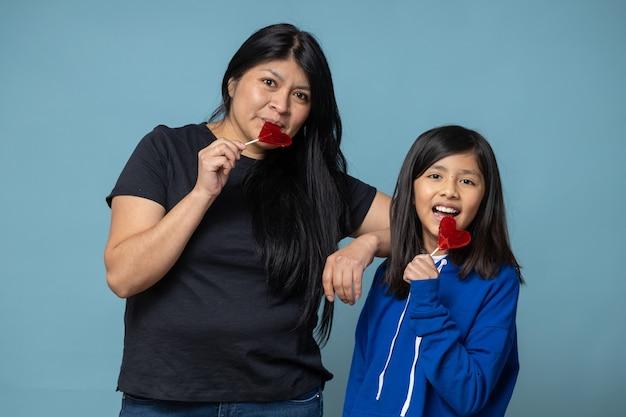 Mexicaanse moeder en dochter die hartvormige lolly delen