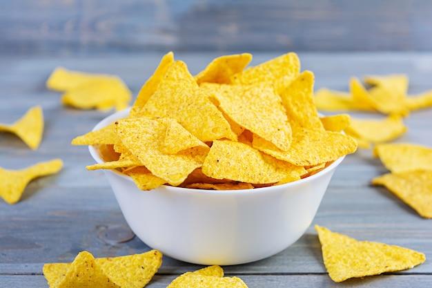 Mexicaanse nacho's met kaas. graanspaanders op houten lijst worden geïsoleerd die