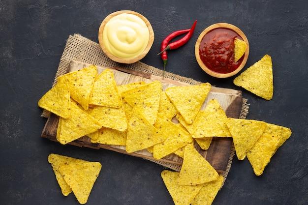 Mexicaanse nacho's van maïs chips met sauzen op donkere achtergrond. bovenaanzicht.
