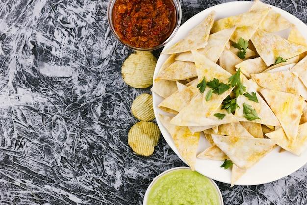 Mexicaanse nachos met kruiden op marmeren achtergrond