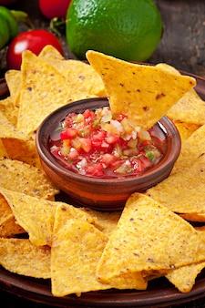 Mexicaanse nachospaanders en salsaonderdompeling in kom op houten