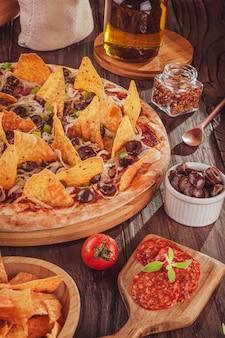Mexicaanse pizza met mozzarella, ui, pepperoni, zwarte olijven, groene paprika, nacho's en oregano (pizza mexicana)