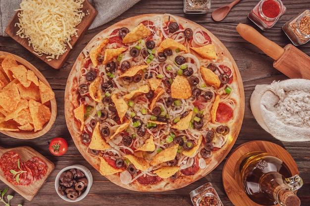 Mexicaanse pizza met mozzarella, ui, pepperoni, zwarte olijven, groene paprika's, nacho's en oregano (pizza mexicana) - bovenaanzicht.