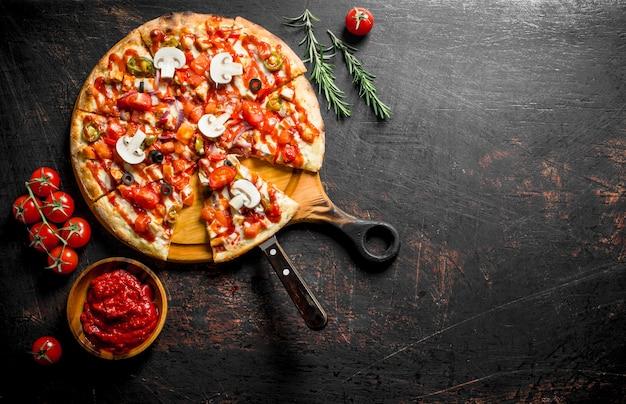 Mexicaanse pizza met rozemarijn en tomatenpuree in kom. op donker rustiek