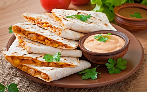 Mexicaanse quesadilla gesneden met groenten en sauzen op de tafel
