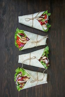 Mexicaanse schotel taco met kip en groentenclose-up op een houten oppervlakte.