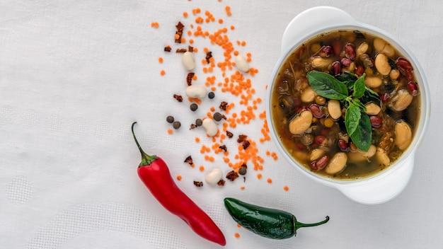 Mexicaanse soep van zeven soorten bonen close-up op een witte linnen achtergrond omringd door rood en groen