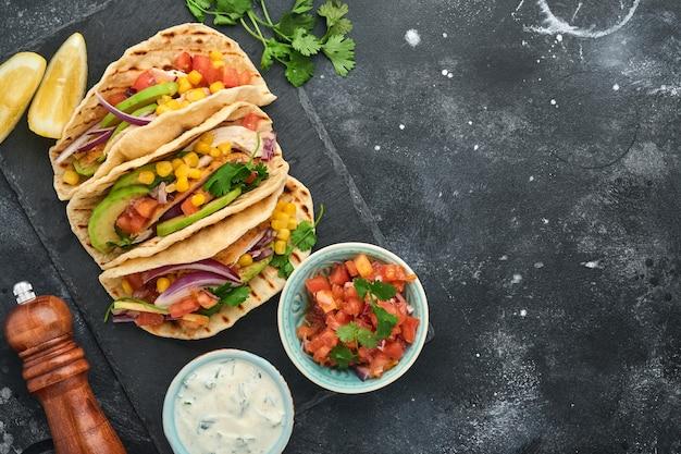 Mexicaanse taco's met gegrilde kip, avocado, maïskorrels, tomaat, ui, koriander en salsa aan zwarte stenen tafel. traditioneel mexicaans en latijns-amerikaans straatvoedsel. bovenaanzicht.