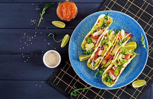 Mexicaanse taco's met kippenvlees, avocado, tomaat, komkommer en rode ui.