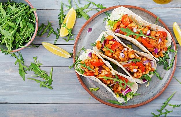 Mexicaanse taco's met rundvlees, bonen in tomatensaus en salsa. plat leggen. bovenaanzicht