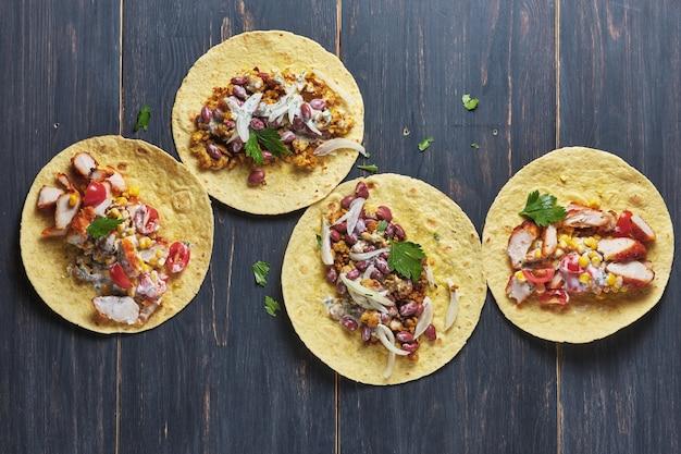 Mexicaanse taco's met saus op een oude houten tafel taco's met bonen, maïs, uien, tomaten en vlees