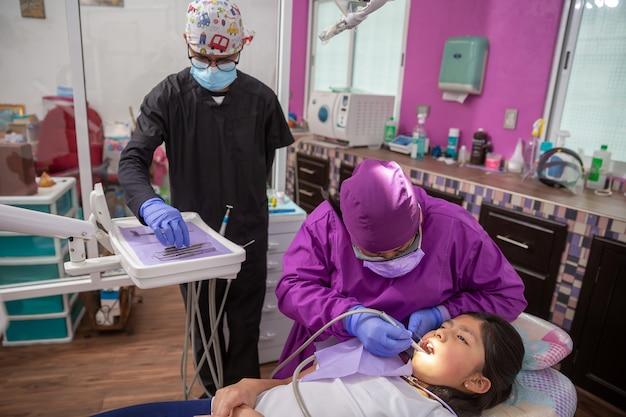 Mexicaanse tandarts, medische controle mondholte van vrouwelijke patiënt met tandheelkundige instrumenten