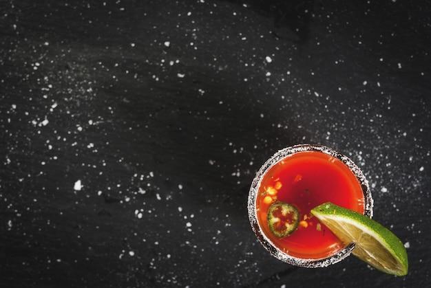Mexicaanse traditionele alcoholische drank. sangrita met tequila tomatensap hete kruiden chili en limoen. analoge bloederige mary. op zwarte leisteen tafel