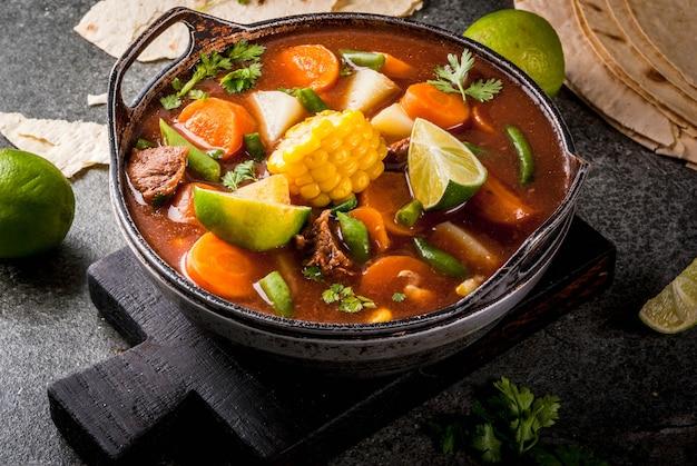 Mexicaanse traditionele groentesoep met vlees, aardappelen, wortelen, bonen, maïs en limoen