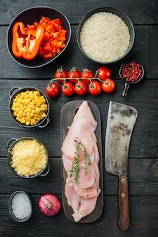 Mexicaanse voedselingrediënten kip enchilada, rijst braadpan, op zwarte houten tafel, bovenaanzicht plat lag