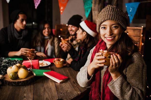 Mexicaanse vrouw die ponche drinkt die een posada in kerstmis mexico viert
