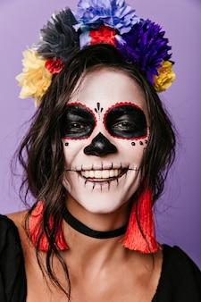 Mexicaanse vrouw in masker in geweldige stemming met sneeuwwitte glimlach, poseren voor close-up portret. Gratis Foto