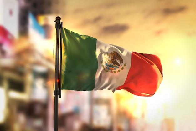 Mexico vlag tegen stad wazige achtergrond bij zonsopgang achtergrondverlichting