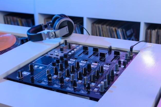 Mezcladora de audio de dj met tocadiscos de vinil en tienda de discos met una mano manipulandola