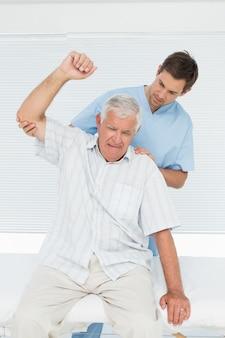 Mhysiotherapist die hogere mens bijstaan om hand op te heffen
