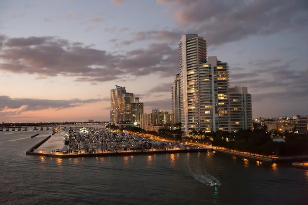 Miami, south beach: moderne gebouwen in de buurt van water in de baai met veel boten bij zonsondergang en verlichtende lichten op bewolkte avondhemelachtergrond, nachtscène