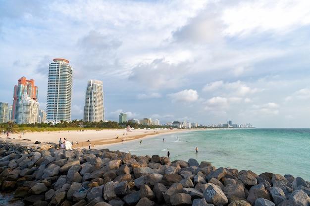 Miami, verenigde staten - 19 april 2021: zeestrand en stadsgezicht. strandresort op stedelijke skyline. kust metropool. toevlucht stad. vakanties aan zee. zomervakantie. reisbestemming.