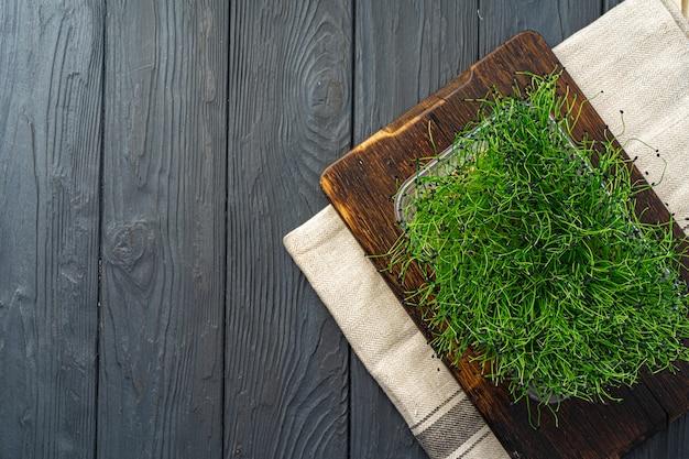 Micro groene spruiten op een houten bord, bekijken van bovenaf