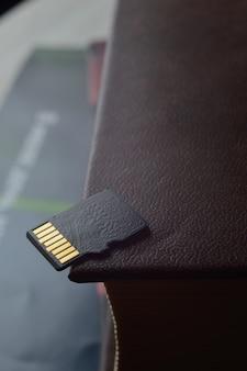 Micro sd-kaart ligt bovenop een papieren boek, gouden contacten bovenaan. detailopname.