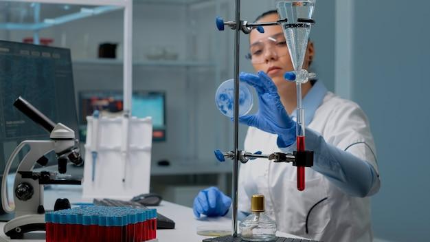 Microbiologievrouw die petrischaal in laboratorium bestudeert
