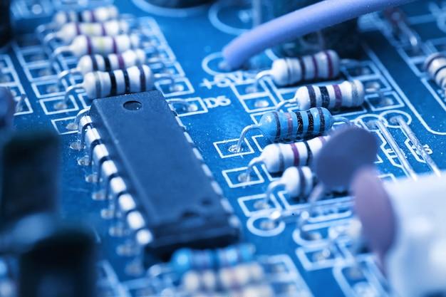 Microchip, condensatoren, weerstanden op een blauw computerbord