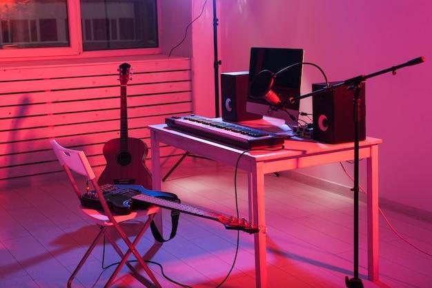 Microfoon, computer en muziekapparatuur gitaren en piano achtergrond. thuis opnamestudio concept.