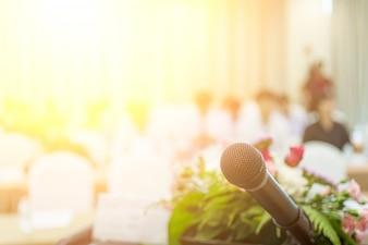 Microfoon dicht omhoog geschoten in seminarie of vergaderzaal met mensen in onduidelijk beeldnadruk voor exemplaarruimte