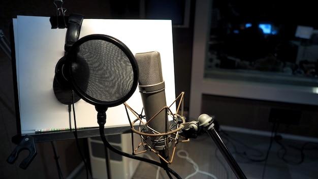 Microfoon met popfilter en schokdempende anti-vibratie en notenstandaard en statief in studioproductie voor muziekpartituren
