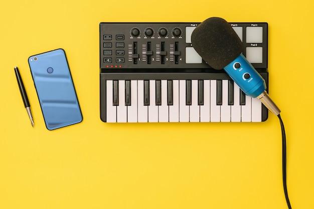 Microfoon, mixer, smartphone en pen op geel oppervlak