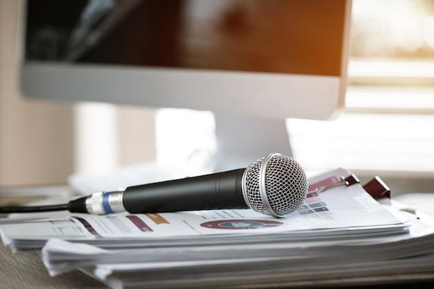 Microfoon op document document bij seminarie voor spreker of lezingsleraar bij klaslokaaluniversiteit
