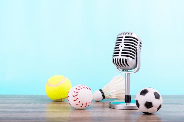 Microfoon op houten tafel met voetbal, tennisbal, honkbal en shuttle op blauwe achtergrondgeluid