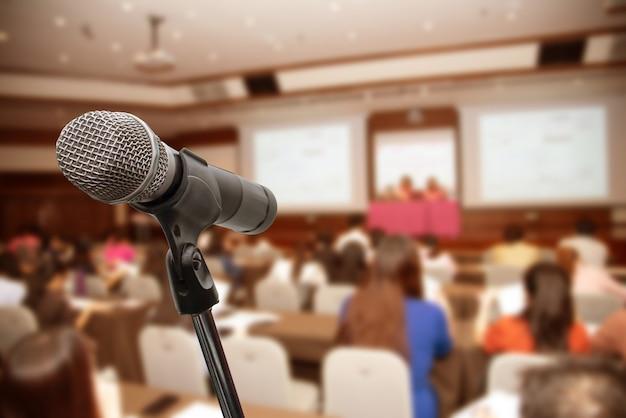 Microfoon over het vage bedrijfsmensenforum vergaderingsconferentie opleiding het leren het trainen concept, vage achtergrond.