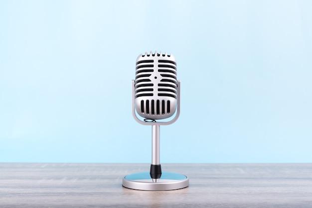 Microfoon retro zet op houten tafel geïsoleerd op blauwe achtergrond.
