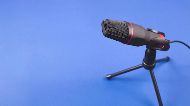 Microfoon voor het opnemen van geluid en podcasts op blauw.
