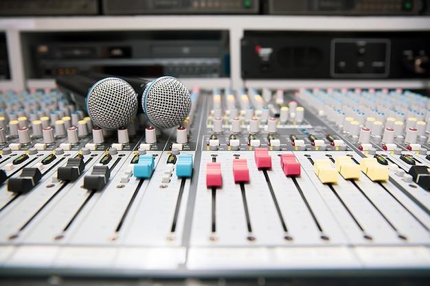 Microfoon wordt op de professionele audiomixer in de studio geplaatst.