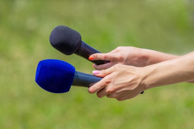 Microfoons in de handen van journalisten tijdens voor nieuwsinterview buitenshuis