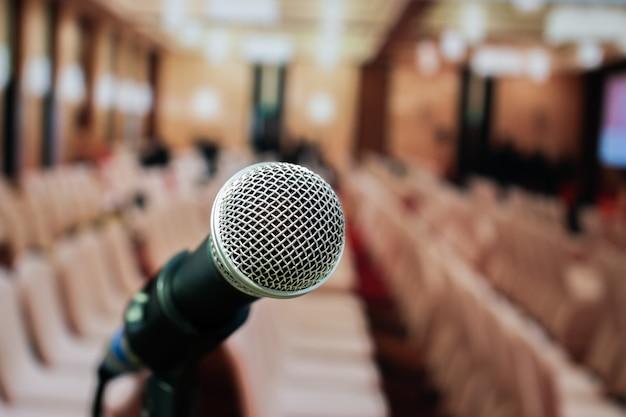 Microfoons op samenvatting vaag van toespraak in seminarieruimte of voorsprekende het spreken conferentiehal