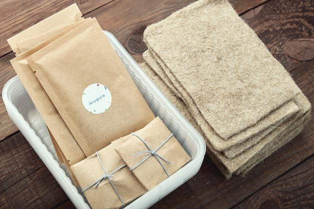 Microgreen aanplant. verpakkingen met zaden, plastic bakjes en linnen matten.