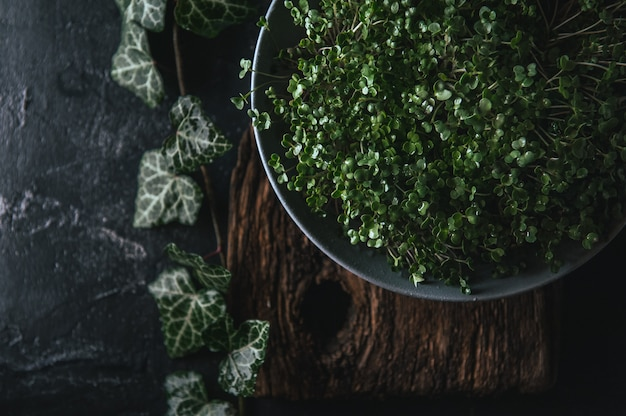 Microgreen in een grijze schotel op een houten plattelander